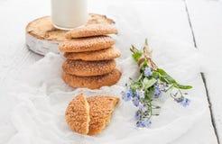 Стог круглых печений shortbread, бутылки молока и bouq стоковые фото