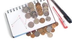 Стог крупного плана монеток, ручки и блокнота на белой предпосылке Стоковая Фотография
