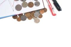 Стог крупного плана монеток, ручки и блокнота на белой предпосылке Стоковые Изображения RF