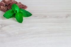 Стог кусков шоколада с лист мяты на деревянном столе Стоковые Изображения RF