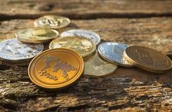 Стог много сияющих секретных монеток на дневном свете в природе на предпосылке деревянного стола Закройте вверх серебряных и золо стоковые фото