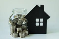 Стог монеток и монеток в стеклянном опарнике с бумажным домом на белизне Стоковая Фотография RF
