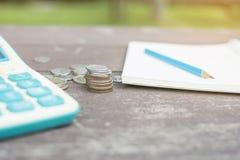Стог монеток с голубым карандашем на пустых финансах и калькуляторе otebook для того чтобы высчитать баланс на деревянном столе Стоковая Фотография RF