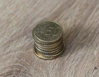Стог 50 монеток цента евро на деревянной предпосылке стоковая фотография