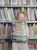 Стог нося девушки книг в библиотеке Стоковая Фотография