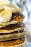 Стог домодельных блинчиков с кусками банана и медом, концом вверх Стоковые Фотографии RF