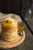 Стог домодельных блинчиков с маслом и медом на деревенской предпосылке Стоковое фото RF