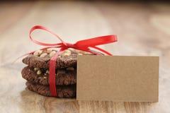 Стог домодельных печений шоколада при фундуки связанные с лентой на деревянной таблице и бумажной карточке Стоковые Изображения RF