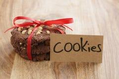 Стог домодельных печений шоколада при фундуки связанные с лентой на деревянной таблице и бумажной карточке Стоковая Фотография