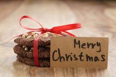 Стог домодельных печений шоколада при фундуки связанные с лентой на деревянной таблице и бумажной карточке Стоковые Фото
