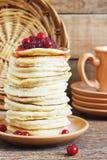 Стог очень вкусных блинчиков с клюквами на предпосылке плиты и салфетки деревянной Стоковое Изображение