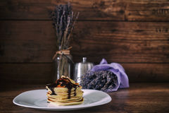 Стог очень вкусных блинчиков с шоколадом, медом, кусками банана и сахаром рицинуса на плите на деревянной предпосылке, ручке цинн Стоковое Фото
