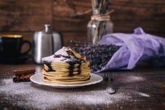 Стог очень вкусных блинчиков с шоколадом, медом, кусками банана и сахаром рицинуса на плите на деревянной предпосылке, ручке цинн Стоковое Изображение RF
