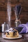 Стог очень вкусных блинчиков с шоколадом, медом, кусками банана и сахаром рицинуса на плите на деревянной предпосылке, ручке цинн Стоковые Фотографии RF