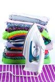 Стог одежды и утюга на белой предпосылке Стоковое Изображение