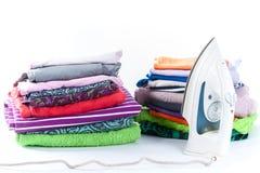 Стог одежды и утюга на белой предпосылке Стоковая Фотография RF