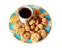 Стог печений обломока шоколада в винтажной голубой плите и чашке чаю Стоковая Фотография