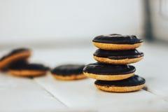 Стог печенья на белой деревянной предпосылке Круглые печенья в поливе шоколада Стойки на одине другого Стоковое фото RF