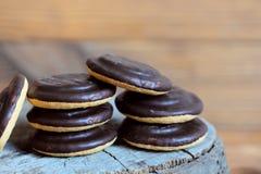 Стог печенья на деревянной предпосылке Круглые печенья в поливе шоколада closeup Стоковая Фотография RF