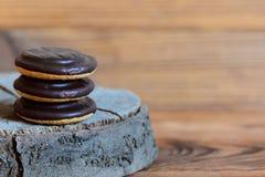 Стог печенья на деревянной предпосылке с космосом экземпляра для текста 3 круглых печенья в поливе шоколада Стоковое фото RF
