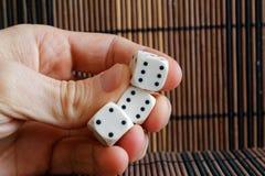 Стог пластмассы 3 белизн dices в руке ` s человека на коричневой предпосылке деревянного стола 6 кубов сторон с черными точками 4 Стоковые Изображения