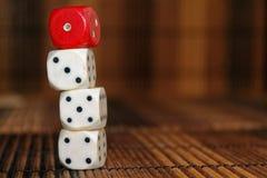 Стог пластмассы 3 белизн dices и кости одного красного цвета на коричневой предпосылке деревянной доски 6 кубов сторон с черными  Стоковые Фото