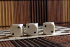 Стог пластмассы 3 белизн dices на коричневой предпосылке деревянной доски 6 кубов сторон с черными точками 2 Стоковая Фотография RF