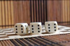 Стог пластмассы 3 белизн dices на коричневой предпосылке деревянной доски 6 кубов сторон с черными точками 6 Стоковые Изображения RF