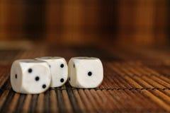 Стог пластмассы 3 белизн dices на коричневой предпосылке деревянной доски 6 кубов сторон с черными точками 1, 3 Стоковое фото RF