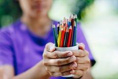Стог покрашенных карандашей в руках Стоковые Изображения