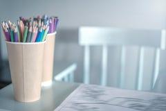 Стог покрашенных карандашей в стекле на таблице детей, рядом с высоким стулом, левым, уютным местом, который нужно нарисовать для стоковое изображение rf