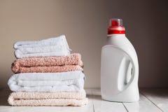 Стог полотенец несколько покрашенных и белых и бутылки с косметическим продуктом Стоковая Фотография