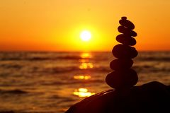 Стог различных камней в балансе на заходе солнца пляжа стоковая фотография