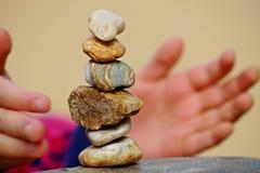 Стог различных камней в балансе с руками ребенка стоковое фото