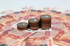 Стог русских коммеморативных 10-монеток на банкнотах предпосылки 5-тысячных Стоковая Фотография