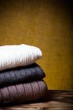 Стог связанных одежд на деревянном столе напротив defocused бушеля Стоковая Фотография RF