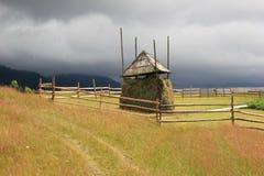 Стог сена на луге горы с бурным небом Стоковая Фотография RF