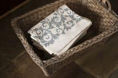 Стог серых салфеток флористического дизайна в прямоугольной сплетенной корзине Стоковая Фотография