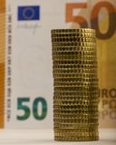 Стог сложенных монеток на предпосылке увяданного бумажного счета f Стоковое Изображение