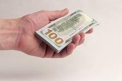 Стог счетов 100-доллара в левой руке человека Персона дает или принимает американские тысячу долларов Взятка или зарплата Стоковые Изображения