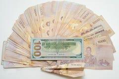 Стог тайского бата и 100 долларов на белой таблице с самолетом стоковое изображение