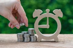 Стог удерживания руки женщины денег монеток кладя на стог монетки Стоковая Фотография