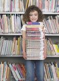 Стог удерживания девушки книг в библиотеке Стоковое Изображение