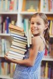 Стог удерживания девушки школы книг в библиотеке стоковое изображение
