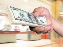 Стог удерживания человека долларовых банкнот Стоковые Изображения