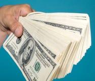 Стог удерживания человека долларовых банкнот Стоковое фото RF