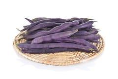 Стог фиолетовых фасолей на подносе ротанга и белой предпосылке Стоковая Фотография