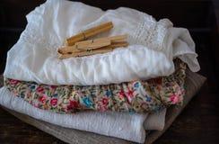 Стог чистых одежд и полотенец белья, зажимок для белья на таблице стоковое изображение