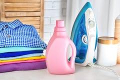 Стог чистых одежд, утюга и бутылки с тензидом Стоковые Изображения RF