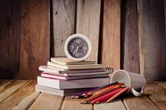 Стог Crayons книг и часов на столе деревянный пол Стоковые Изображения